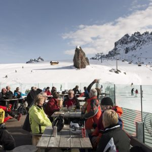 People relaxing at the sun in the terrace of Rifugio Cesa da Fuoch at Porta Vescovo Dolomiti Resort,Arabba